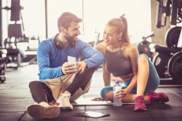 Personal trainer with young sports girl sitting on floor and having conversation after exercise using mobile phone